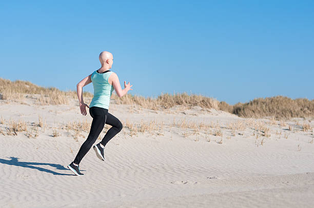 young woman with bald head jogging after chemotherapy stock photo