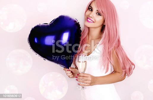 istock Young woman with balloon and glass of champagne 1016582612