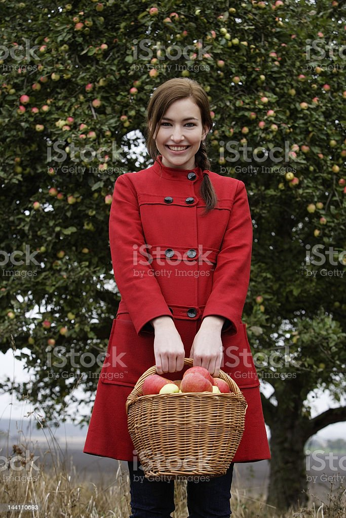 Young woman with basket full of apples royalty-free stock photo