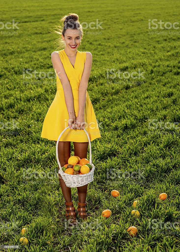 Young woman with basket full of fruits smiling on greenfield of grass...
