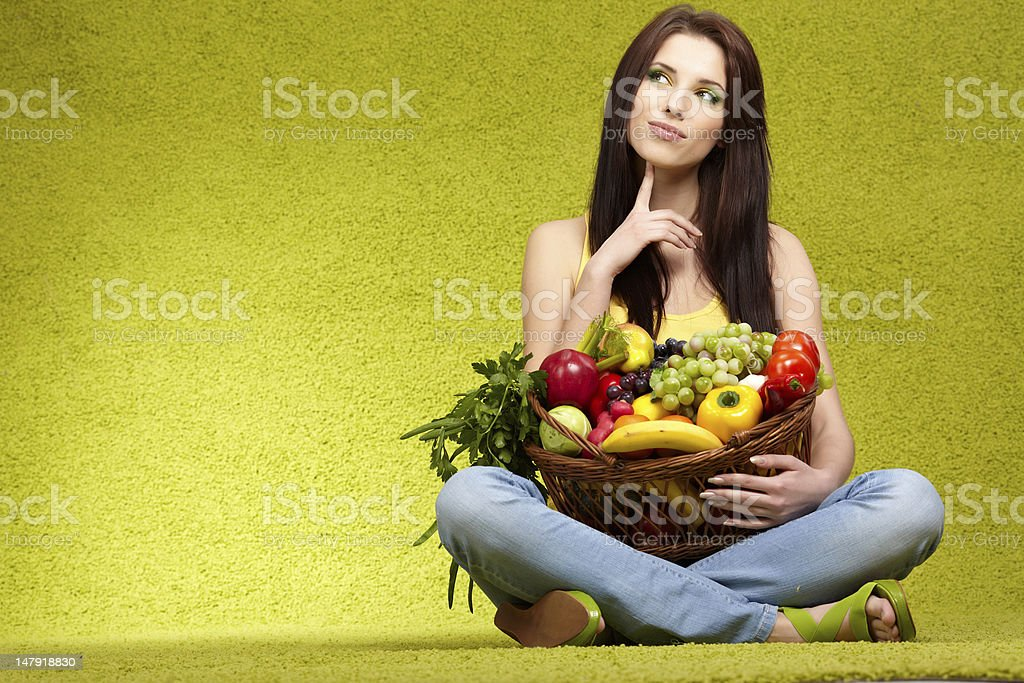 Young woman with basket of fruits and vegetables stock photo