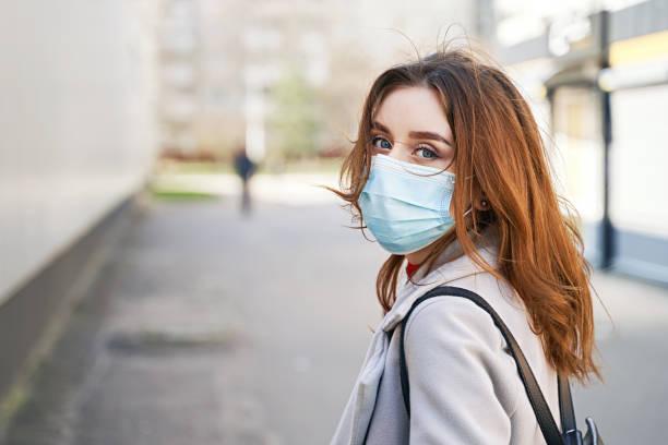 Young woman with beautiful blue eyes and disheveled hair wearing protection face mask against coronavirus MERS-Cov, Novel coronavirus 2019-nCoV. Concept of coronavirus quarantine and pandemic. stock photo