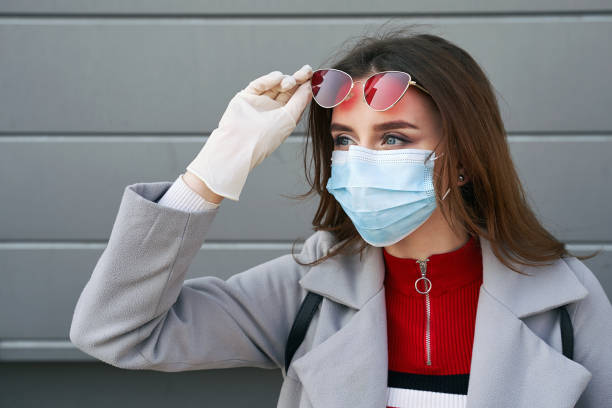 Young woman with beautiful blue eyes wearing protection face mask against coronavirus MERS-Cov, Novel coronavirus 2019-nCoV on grey wall backgorund. Concept of coronavirus quarantine and pandemic. stock photo