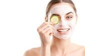 Close-up shot of a smiling beautiful young woman wearing a face mask and holding a cucumber slice in front of her eye. Isolated on white background.