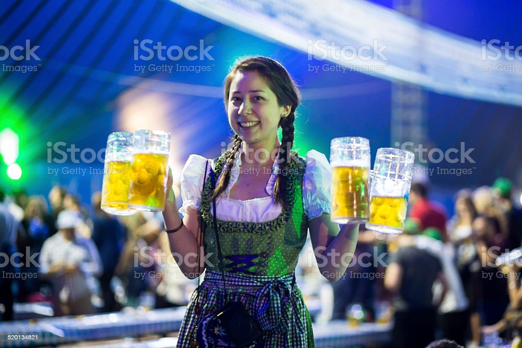 Young woman with beer steins at Oktoberfest stock photo