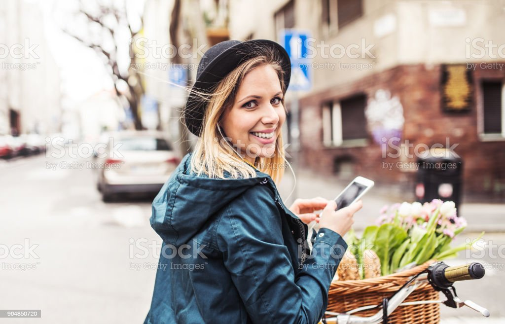 Young woman with bicycle and smartphone in sunny spring town. royalty-free stock photo