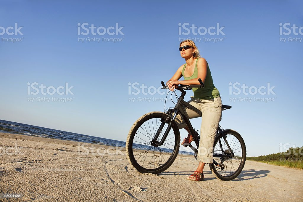 Young woman with bicycle in beach royalty-free stock photo