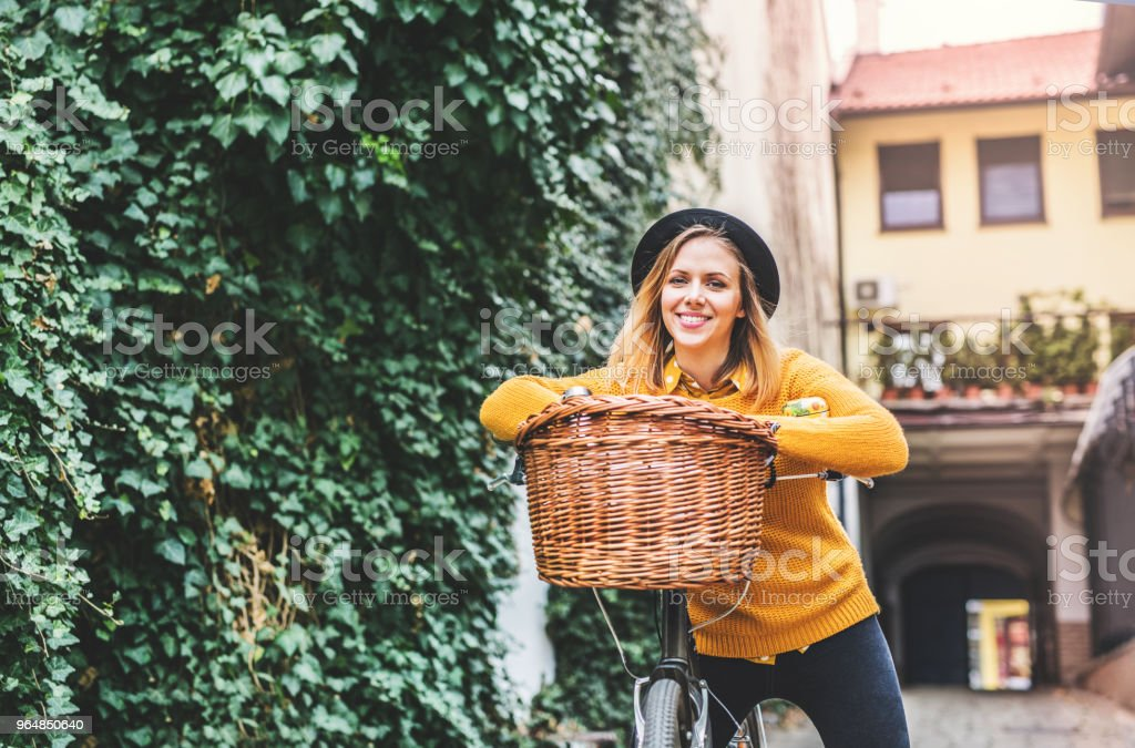 Young woman with bicycle in sunny spring town. royalty-free stock photo