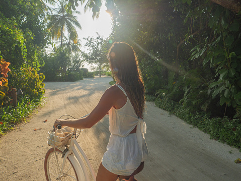 Tropical vacations young woman with bicycle in the Maldives contemplating sunset on the island. Female enjoying bike ride on sandy island. Dreamlike destination