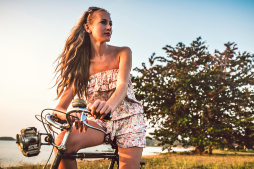 Young woman with bicycle on the beach