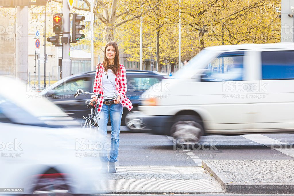 Young woman with bicycle waiting to cross the street stock photo