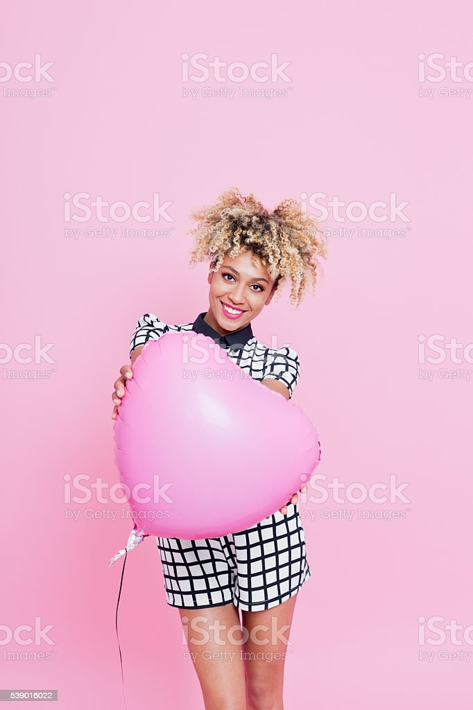 Young woman with big pink heart Portrait of beautiful afro american young woman wearing grid check playsuit, standing against pink background and holding Pink Heart Balloon. 20-24 Years Stock Photo