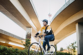 istock Young Woman With Bike and Messenger Bag in The City 1185940456