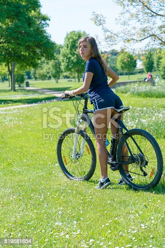 Young woman with bike in green summer park