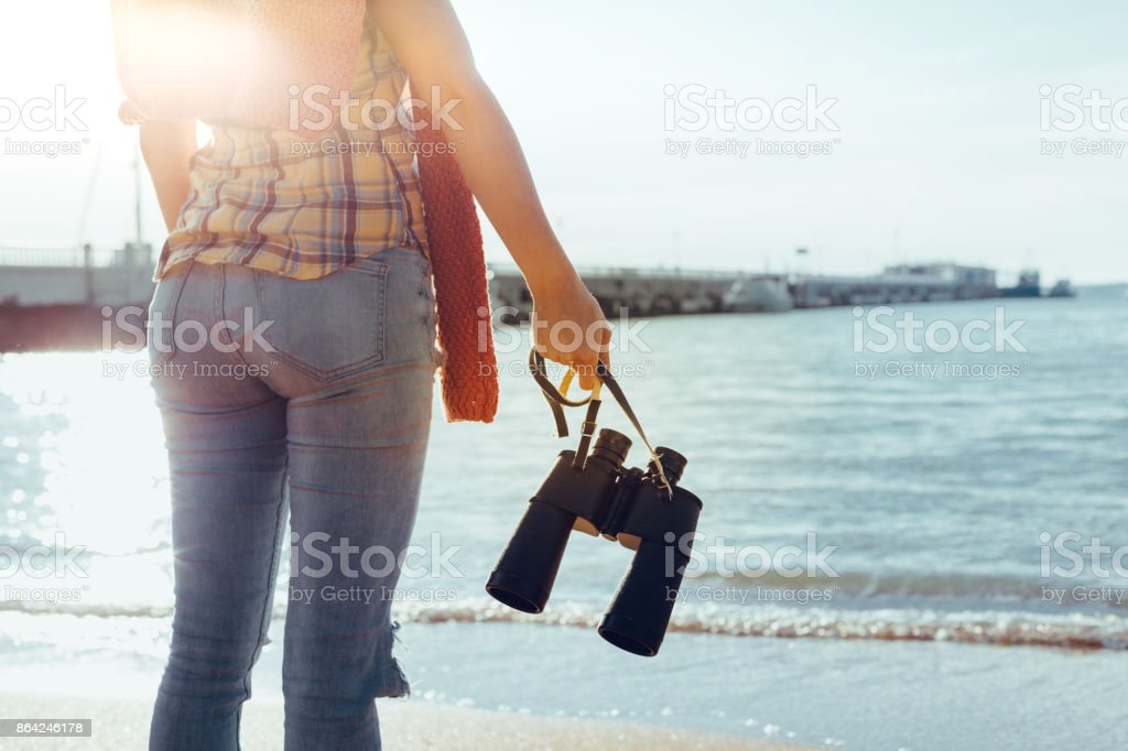 Young Woman With Binoculars In Hand Standing By The Sea And Enjoying View Of Nature, Rear View royalty-free stock photo