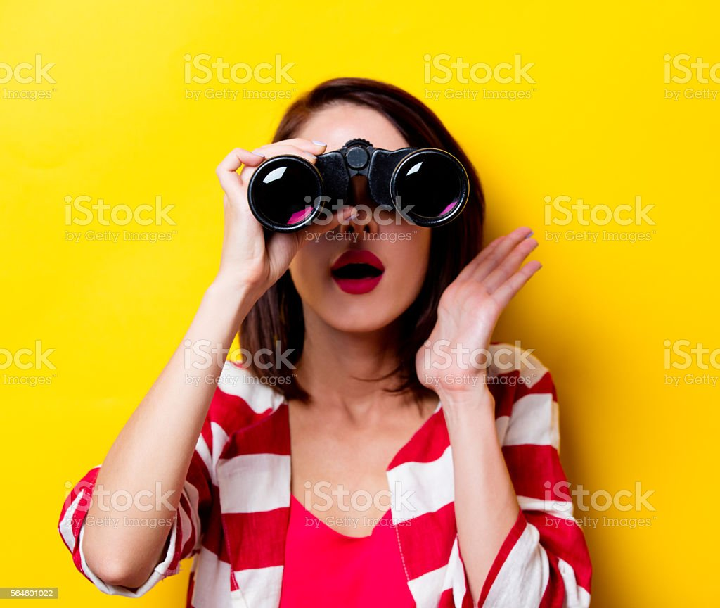 young woman with binoculars stock photo