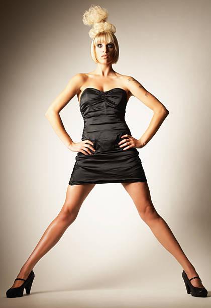 joven mujer con vestido negro y wild estilo de pelo - piernas abiertas mujer fotografías e imágenes de stock