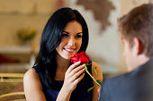 Young woman with black hair being given a red rose