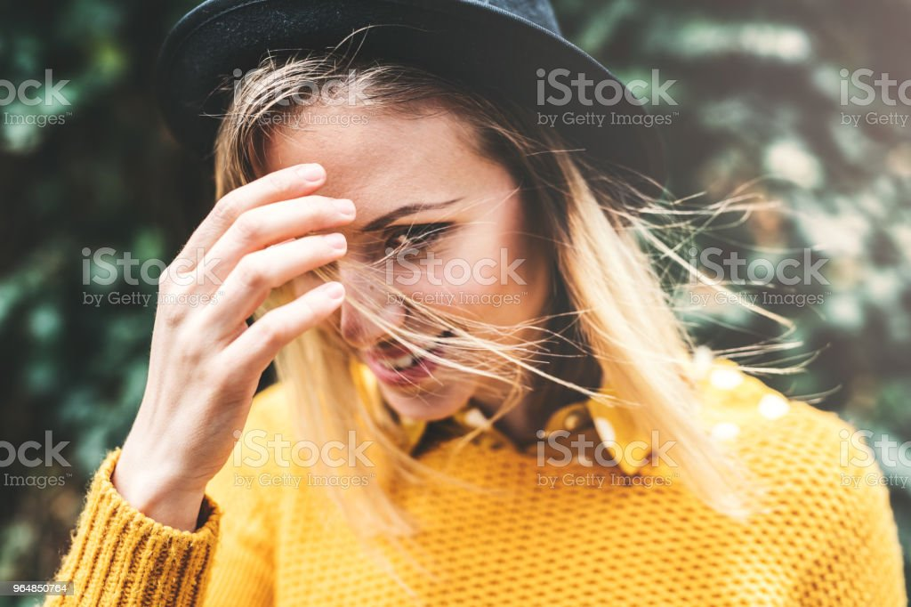 Young woman with black hat standing against a green background in sunny spring. royalty-free stock photo