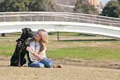 Young woman sitting and embracing her dog black labrador in Trinity Park in Ft Worth, Texas.