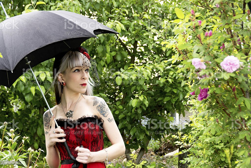 Young woman with black umbrella looking at roses. royalty-free stock photo