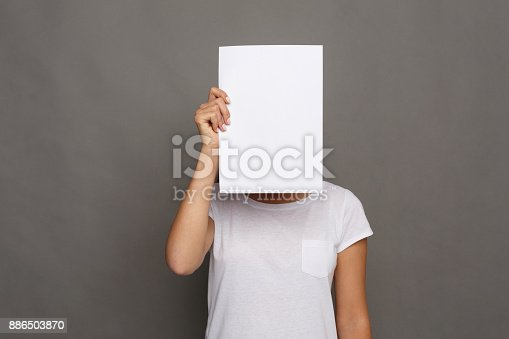 istock Young woman with blank white paper at face 886503870