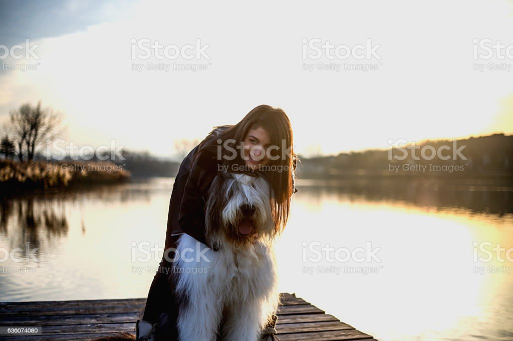 Young woman with Bobtail male dog on the pier stock photo