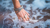 Woman with bohemian style silver rings and bracelets and her hand in the sea water