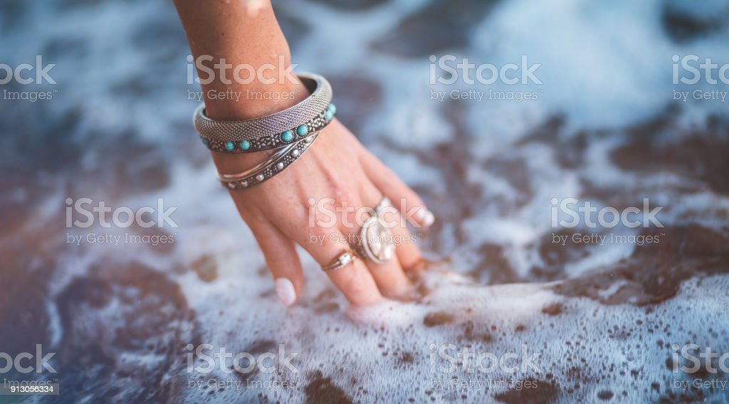 Young woman with boho style jewelry at the beach stock photo