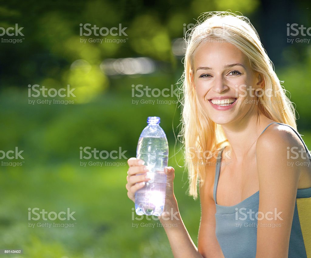 Young woman with bottle of water outdoors royalty-free stock photo