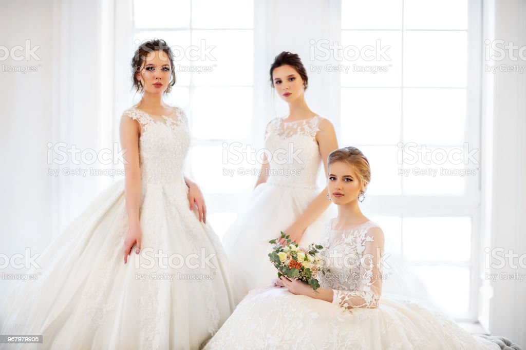 Young woman with bouquets wearing wedding dresses stock photo