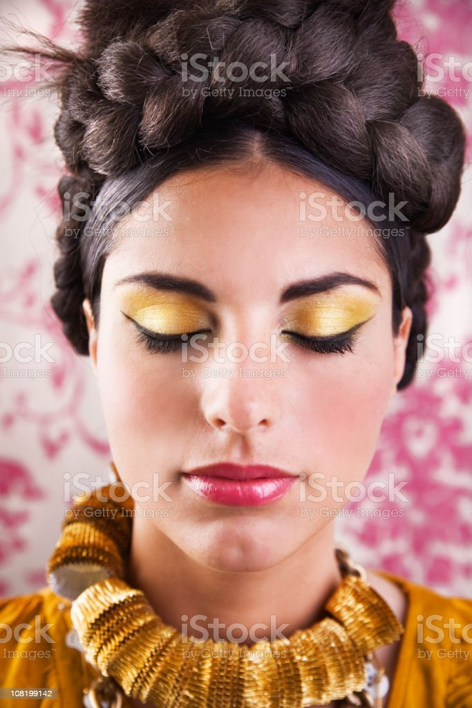 Young Woman with Braided Bun and Make-Up Closing Eyes stock photo