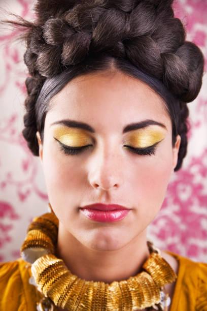 junge frau mit geflochtenen brötchen und make-up der augen schließen - goldenes augen make up stock-fotos und bilder