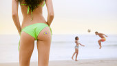 Young woman with Brazil flag tattoo watching couple playing football