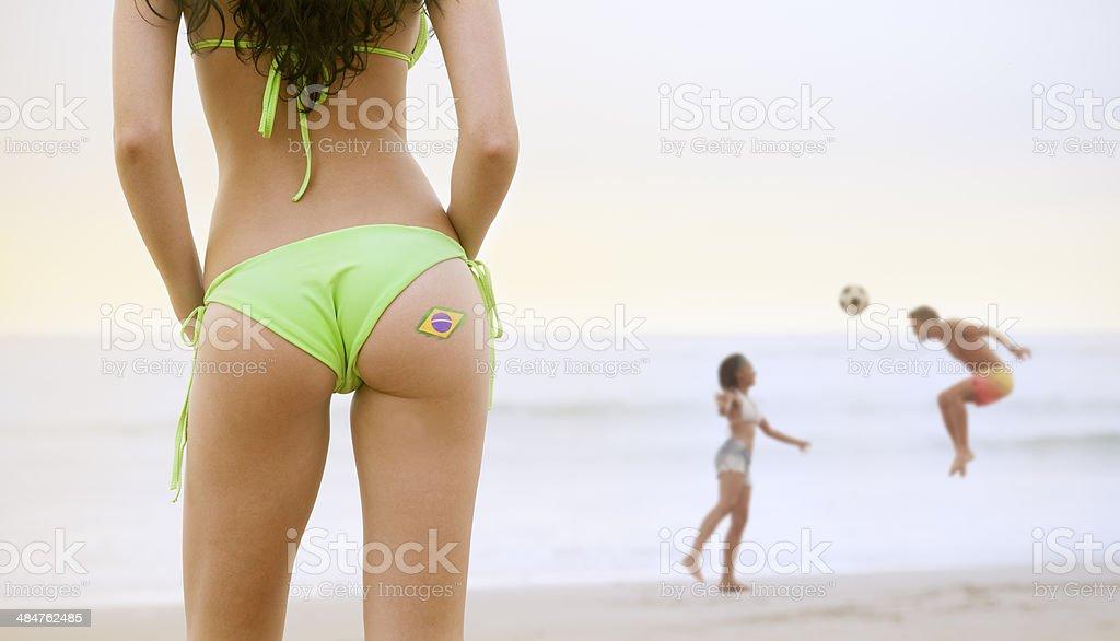 Jovem mulher com bandeira do Brasil tatuagem assistindo casal jogando futebol - foto de acervo