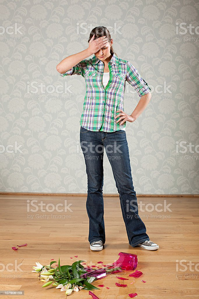 Young woman with broken vase of flowers on floor stock photo