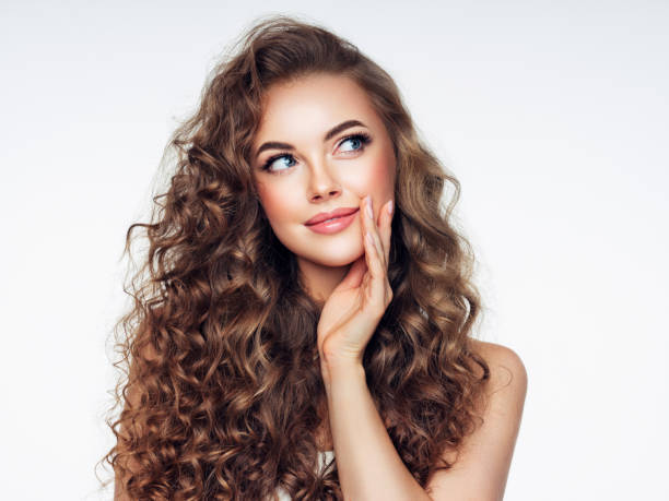 Young woman with brown voluminous and curly hair stock photo