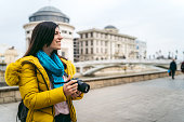 Young Caucasian woman standing on street in Skopje with camera.