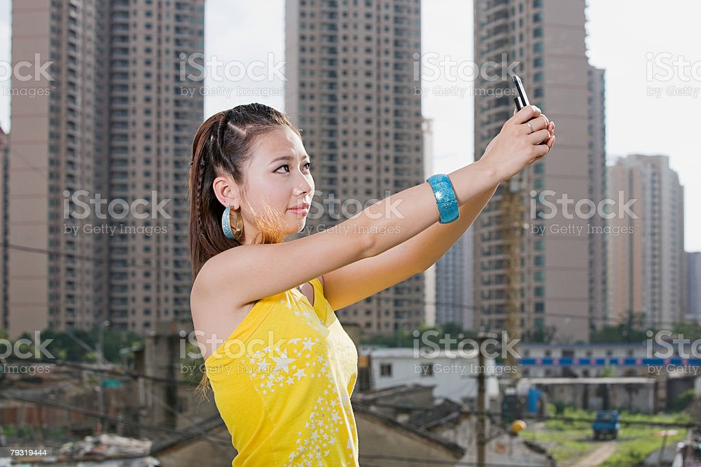 Young woman with camera phone in city royalty-free 스톡 사진