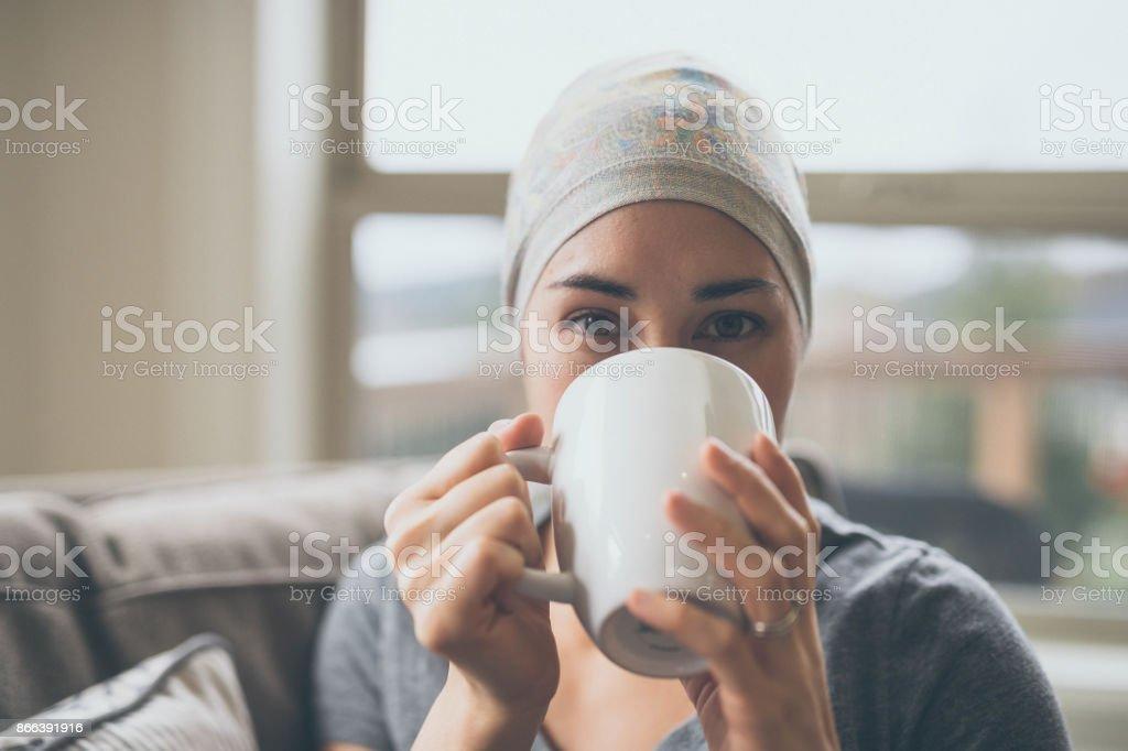 Mujer joven con cáncer tomando té en su salón - foto de stock
