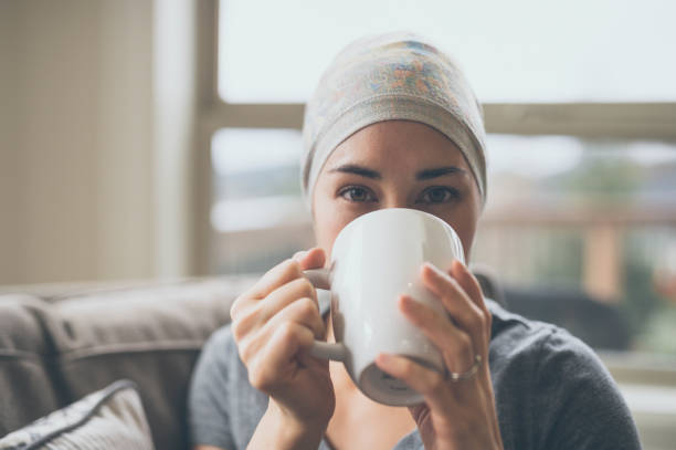 Young woman with cancer drinking tea in her living room stock photo