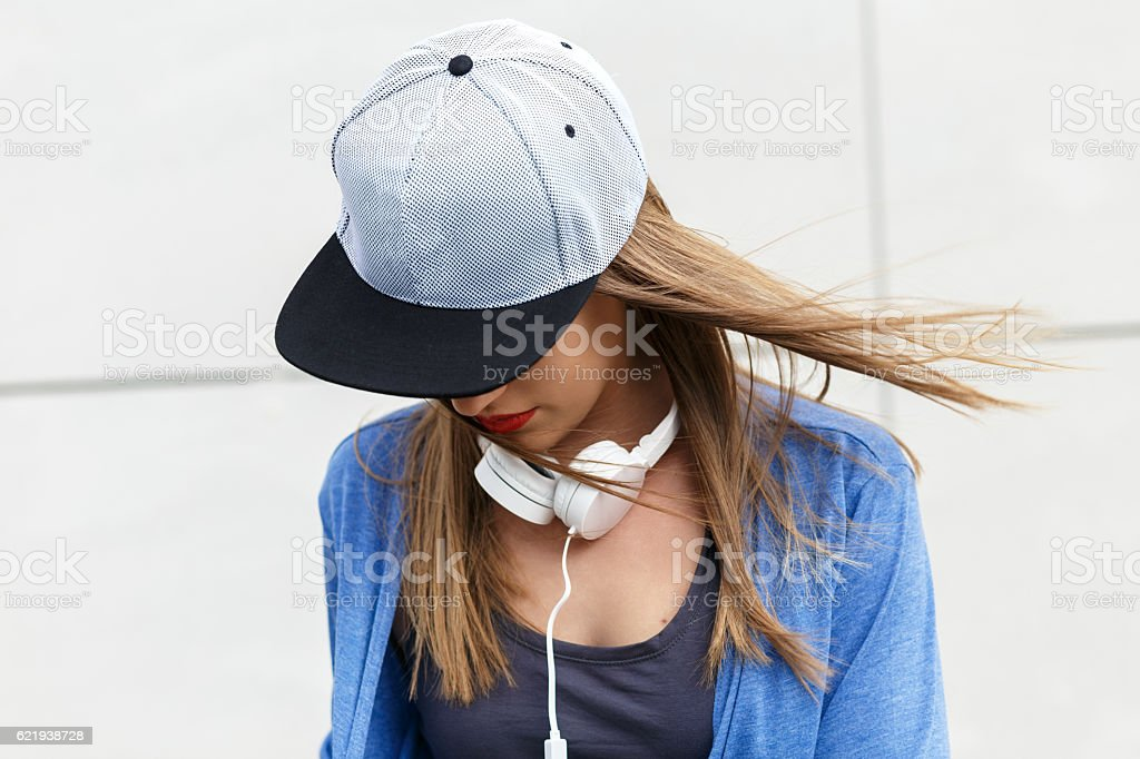 Young woman with cap and headphones stock photo