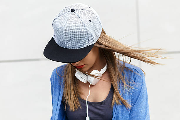 Young woman with cap and headphones Portrait of young woman with cap and headphones looking down. baseball cap stock pictures, royalty-free photos & images