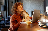 Young woman with cat using laptop