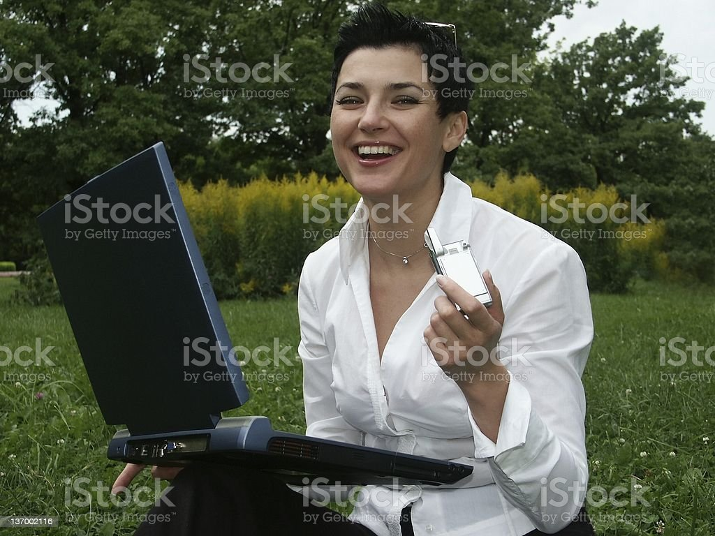 young woman with cell phone  working on laptop royalty-free stock photo