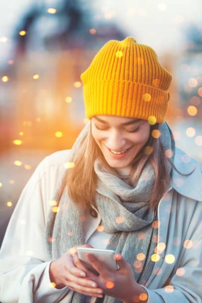 Junge Frau mit Handy unter Weihnachtsbeleuchtung – Foto