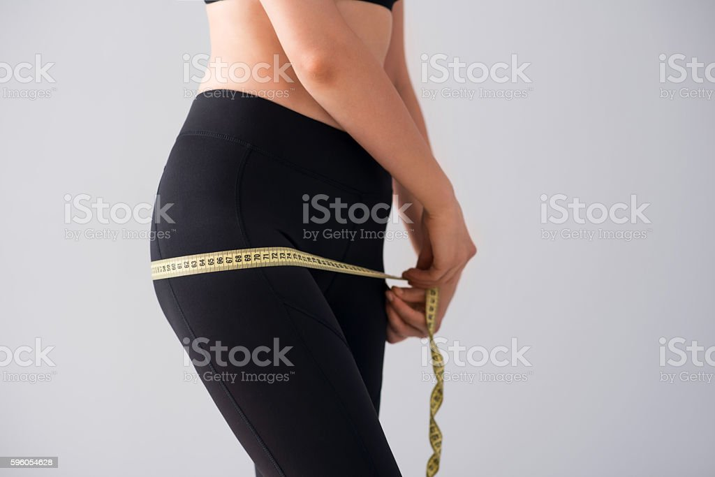 Young woman with centimeter royalty-free stock photo