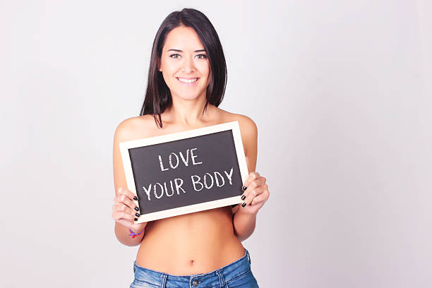 young woman with chalkboard that says love your body - herz zitate stock-fotos und bilder