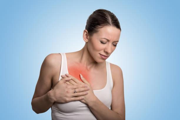 junge frau mit brustschmerz in rot gefärbt isoliert auf blauem hintergrund - symptome brustkrebs stock-fotos und bilder
