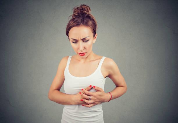 junge frau mit brustschmerzen in der brust abtasten einen klumpen - symptome brustkrebs stock-fotos und bilder